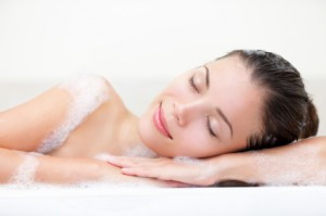 woman relaxing in bath with serene smile and closed eyes full of bath foam. Beautiful young multiracial Caucasian / Asian Chinese female model.