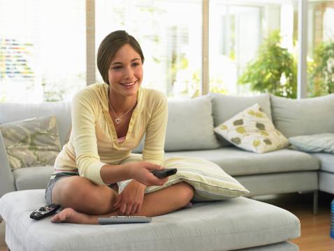 Teenage girl (14-16) watching television, smiling